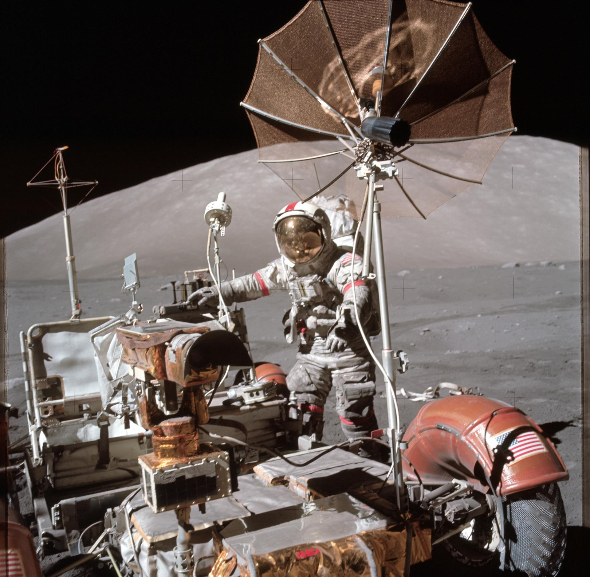 Astronaut standing beside lunar rover on the moon