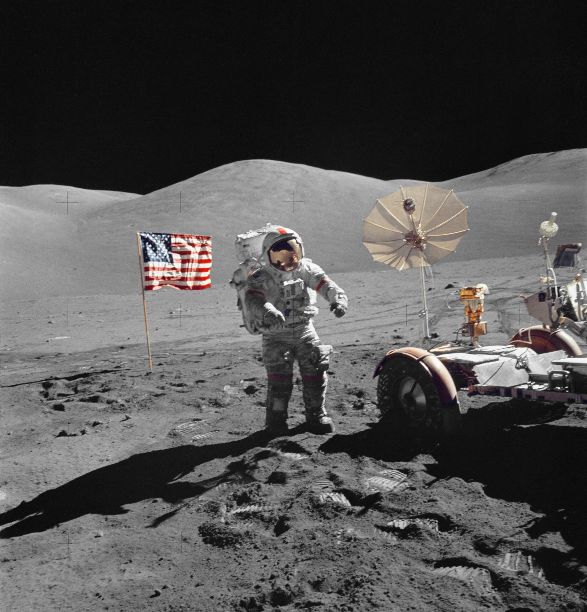 US flag and astronaut with lunar rover on the moon