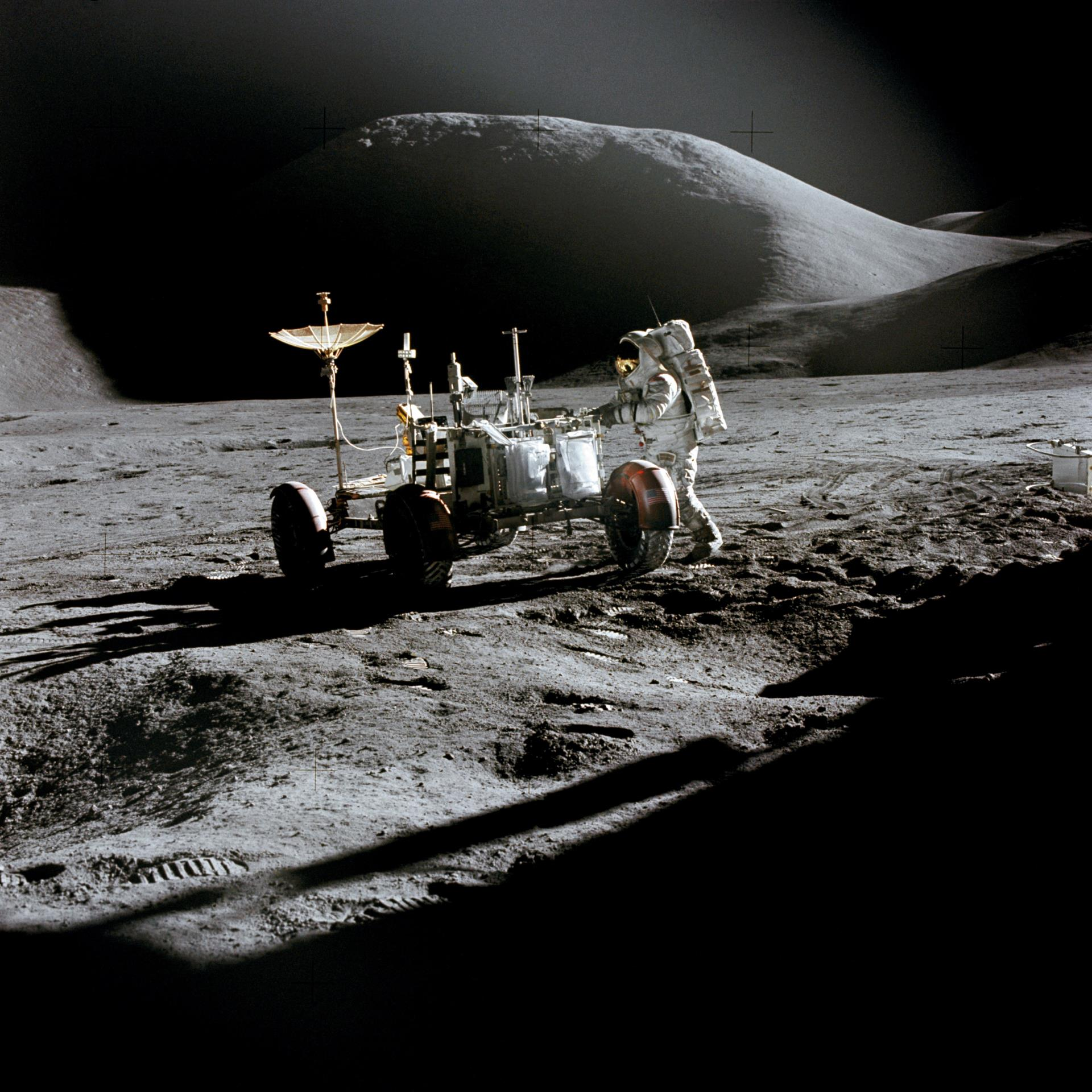 Astronaut working beside rover on moon